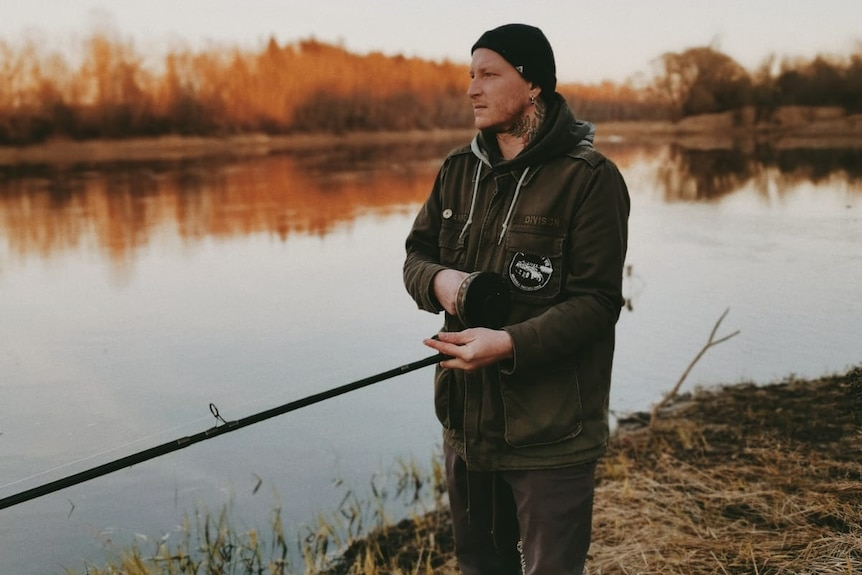 A fisherman standing next to the sea with his fishing rot in Latvia.