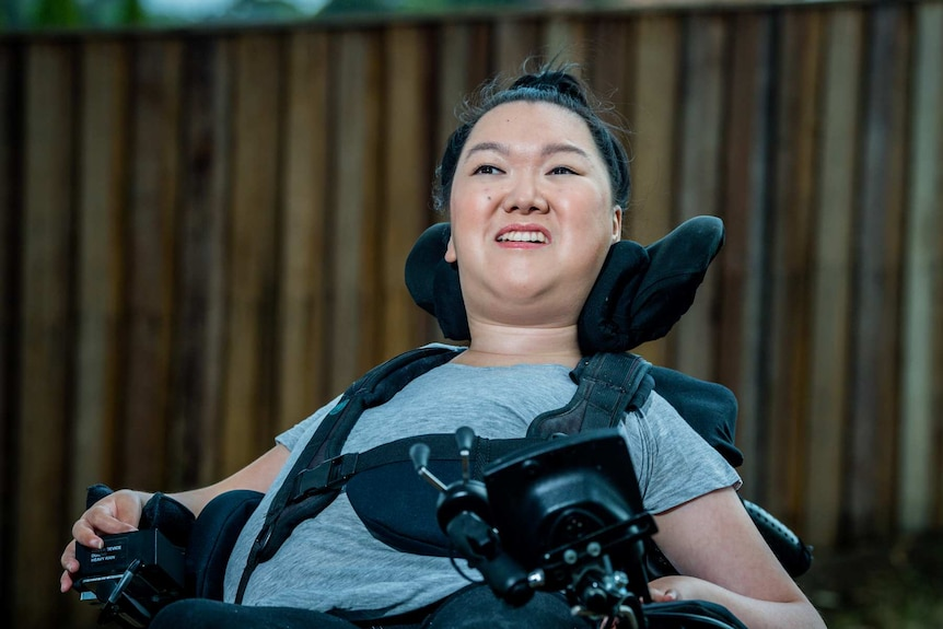 Melanie Tran sits in her wheelchair in front of a wooden fence.