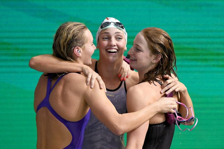 Three young white women in bathers hug