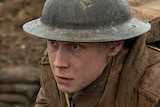 A man in world war one brown uniform, helmet and rifle stands at the edge of trench looking into distance on a rainy day.