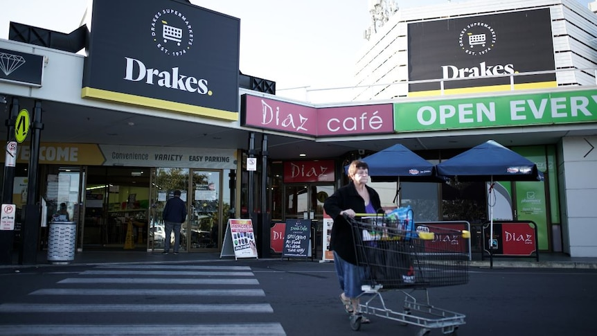 A woman waling behind a trolley in front of a Drakes Supermarkets store