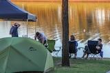 Campers sitting near a dam.