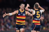 Two AFL players go to give each other a hug after a goal is kicked.