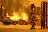 An orange-lit sky with a woman standing watching a blaze that has damaged a property.