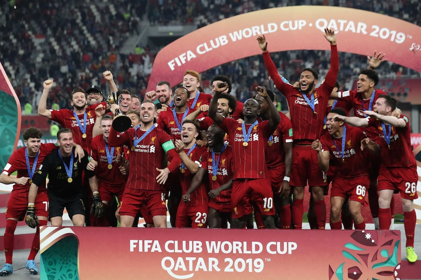 Soccer players jump up and down on a stage with the trophy after winning the Club World Cup.