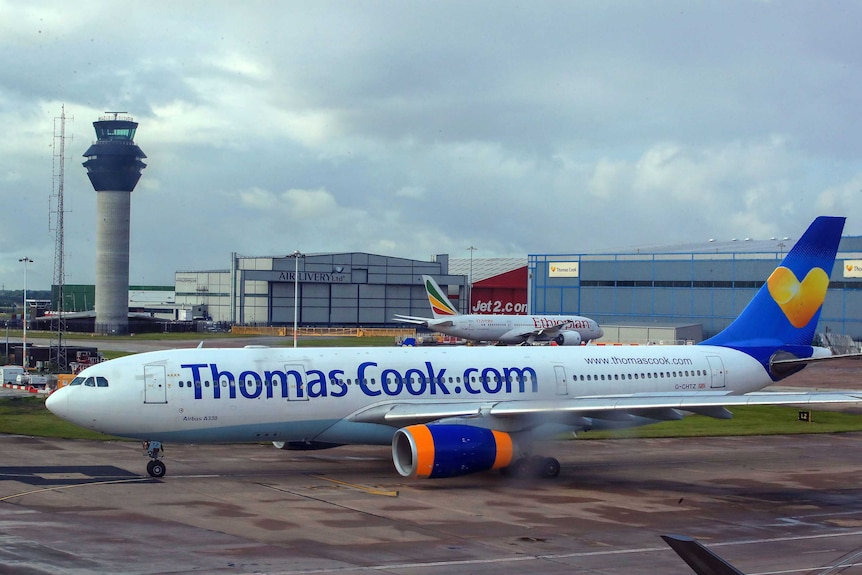 A plane with the words Thomas Cook written on the side in a dark blue font.