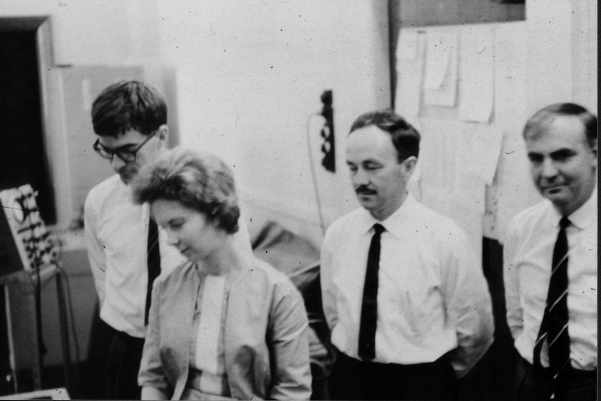 The four members of the CSIRAC staff in the lab looking towards the computer, which is out of shot