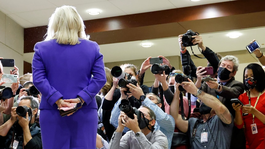 A  blonde woman in a purple skirt and blazer faces a mob of reporters with cameras