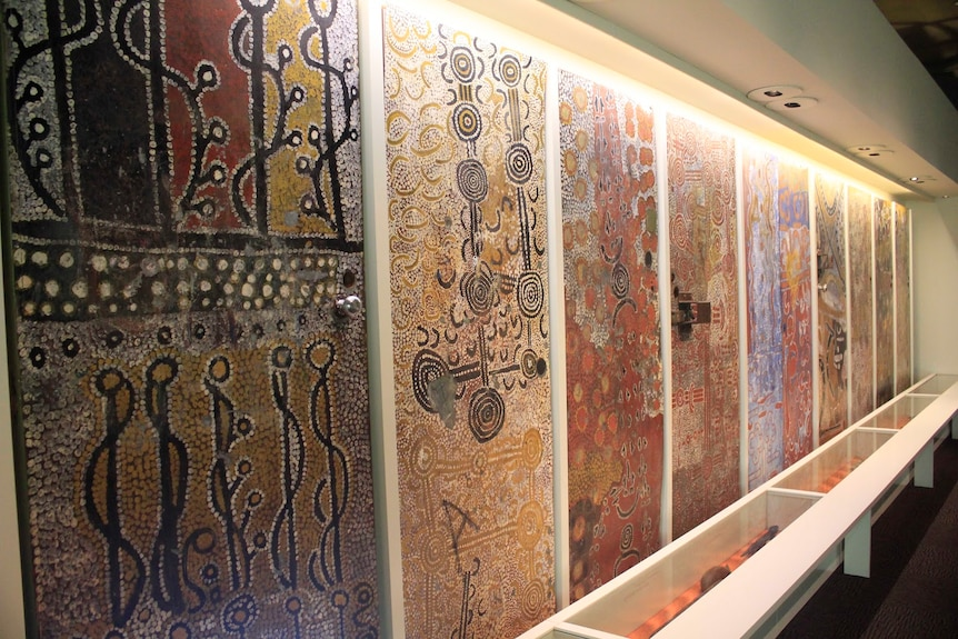 A series of nine doors painted with intricate Aboriginal designs, in a line along a gallery wall