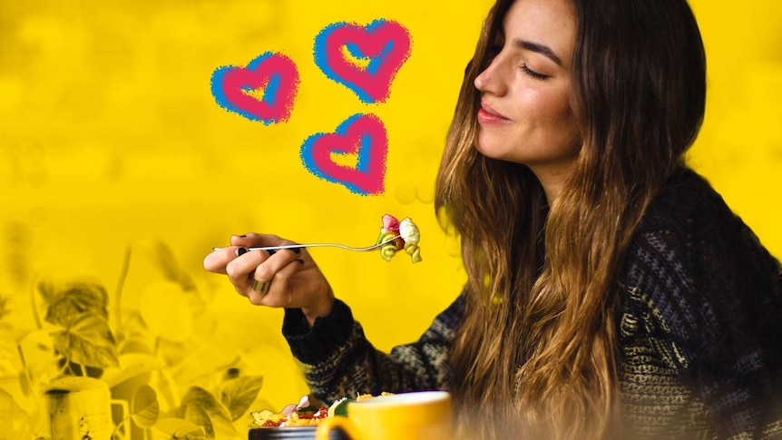 A woman sits alone eating a meal with her eyes closed and a smile on her face against a yellow background with hearts