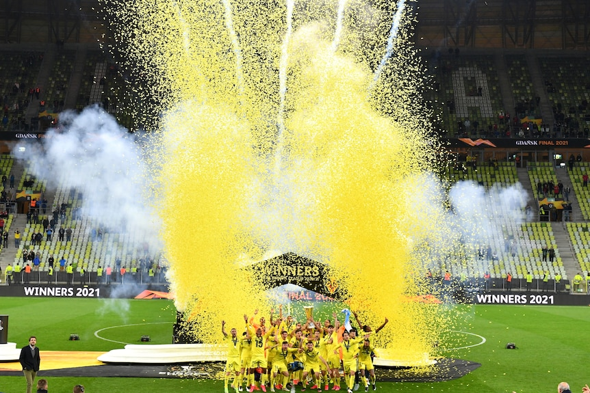 Yellow confetti flies in the air as Villarreal players celebrate with the trophy after winning the Europa League final.