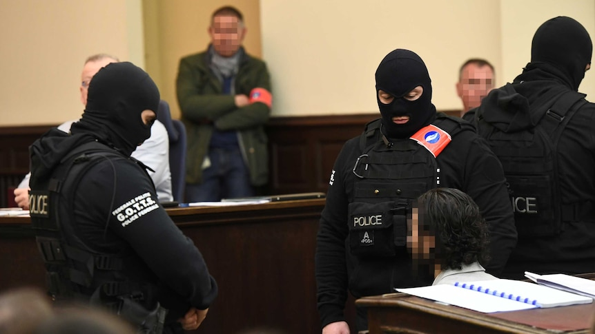 Guards with facemask stand next to Salah Abdeslam, whose face is pixelated.