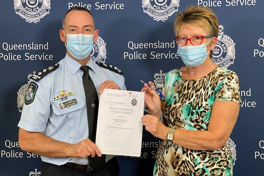 A police officer and a woman in red glasses gilding a piece of paper