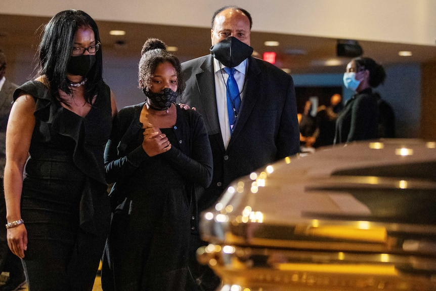 Two African American women and a man look at a gold coffin while wearing black masks