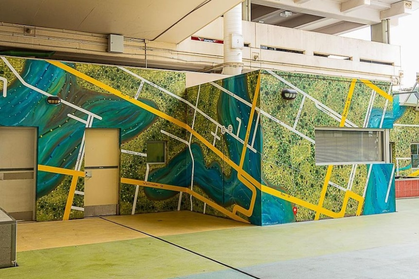 blue, green and yellow mural on a multi-faceted wall in an underground passageway