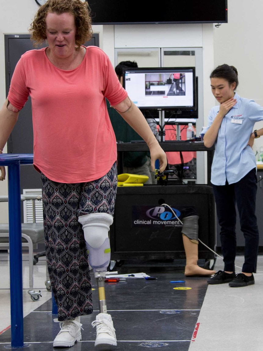 A woman walks on prosthetic legs down a black marked walkway in a white room. Younger woman in blue shirt watches attentively.
