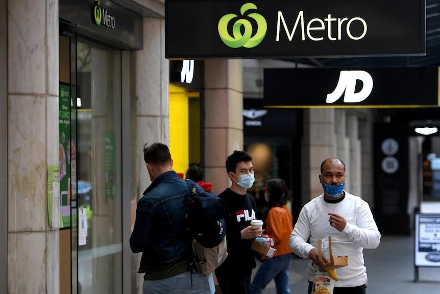 people wearing masks outside a shop