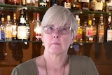 Diane Loechel stands behind a bar with lots of alcohol bottles. She has a serious expression.