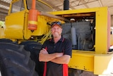 Farmer Colin Penny standing in front of a modified tractor