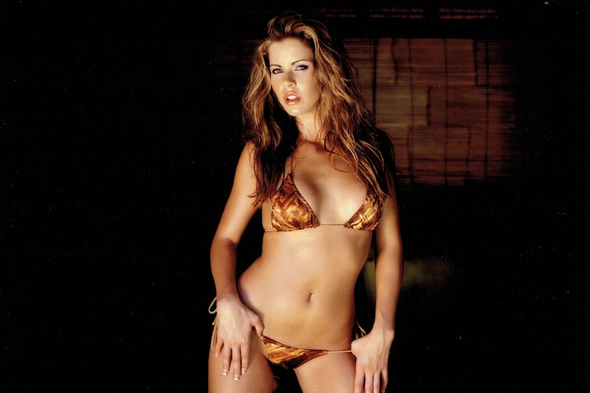 Ricci poses in a bikini, kneeling on what appears to be a mattress in a darkened room.