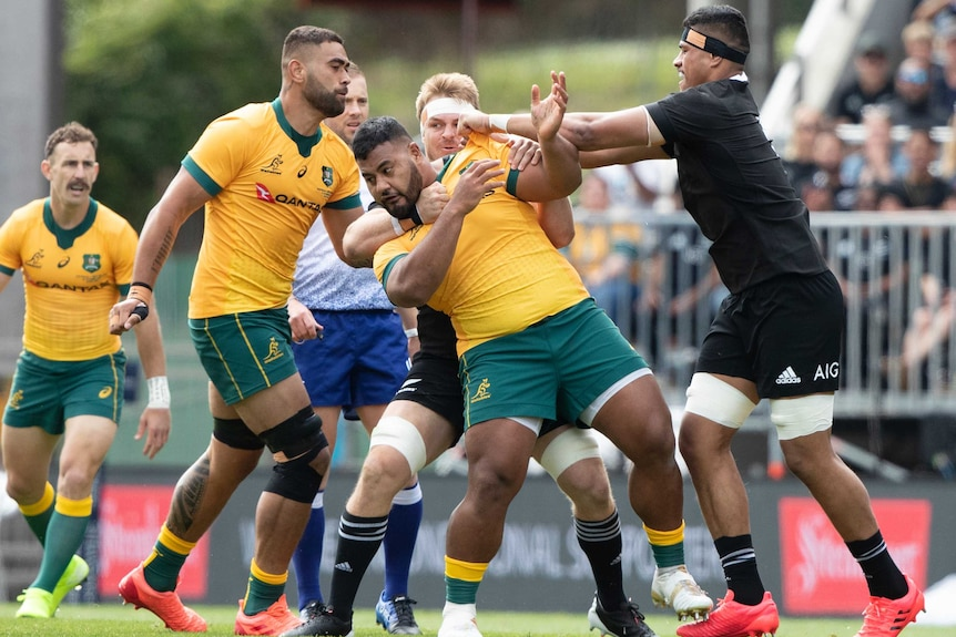 A New Zealand All Blacks players holds an Australian Wallabies opponent around the shoulders.