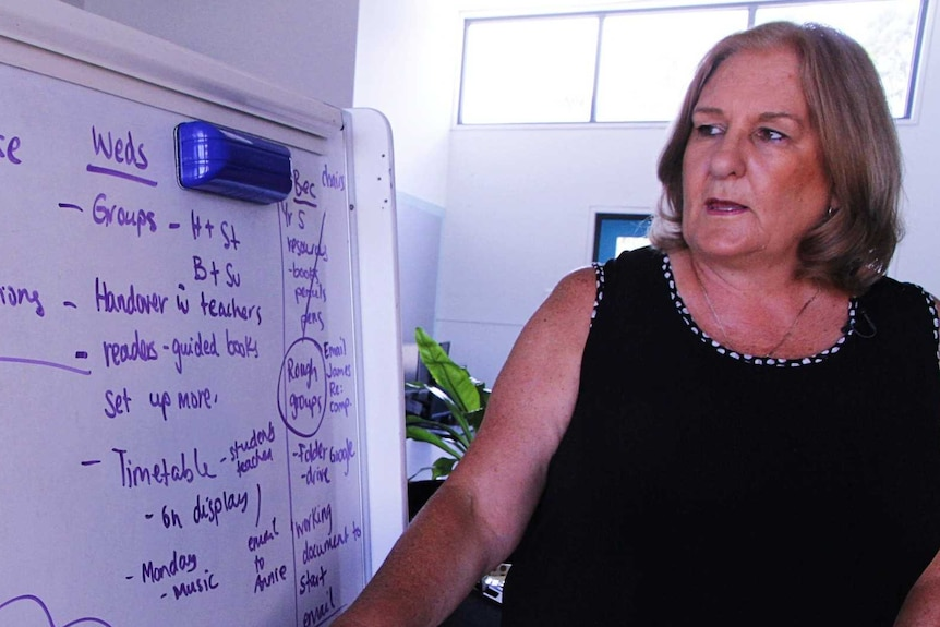 A woman stands at a whiteboard pointing to text about keeping doors open.
