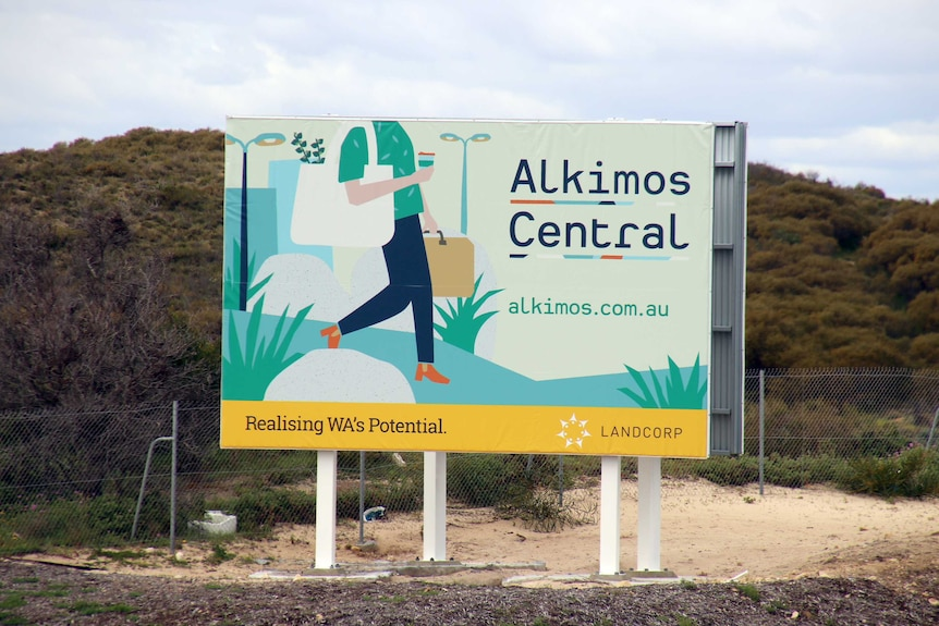 A sign advertising Alkimos Central sits on a large area of vacant land.
