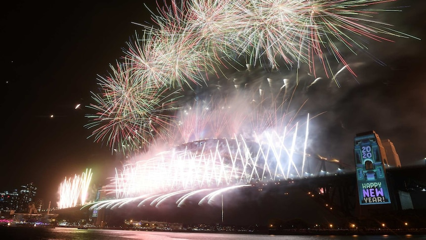 a bright fireworks display on the harbour bridge shot from a low angle