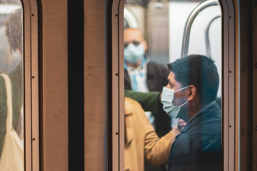 Passengers on a train wear masks during the COVID-19 pandemic.