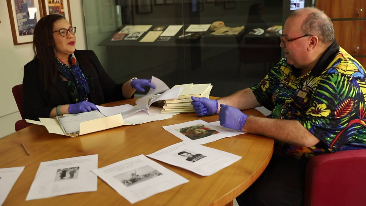 Danusha Cubillo and Michael Bell sit at a desk wearing gloves, with historical documents in front of them.