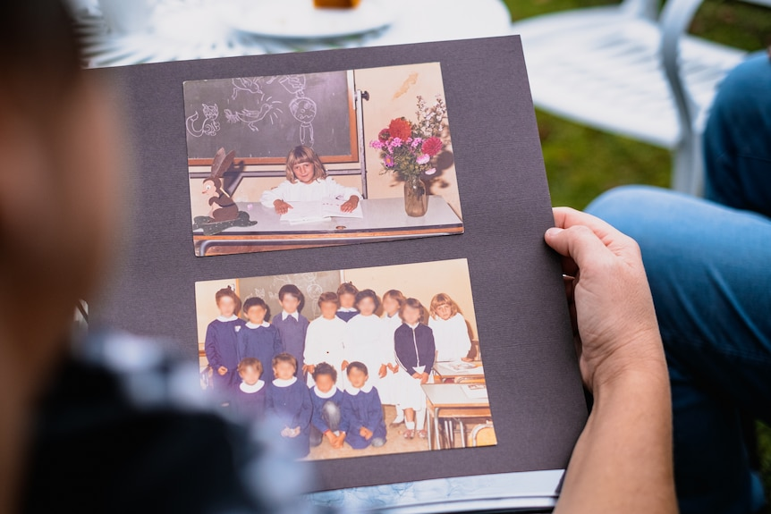 A shot over Renee's shoulder of her looking at a photo album