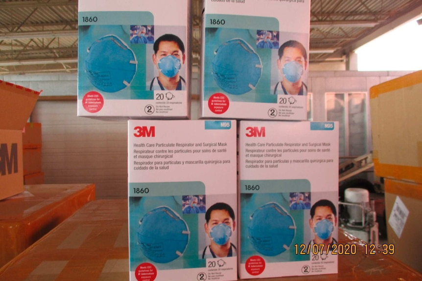 Four boxes of counterfeit medical-grade face masks are stacked on top of boxes in a warehouse.