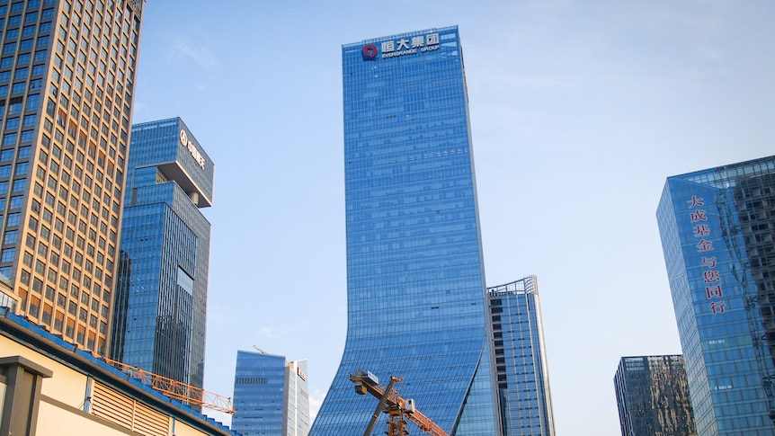 A building soaring into a blue sky, with a crane in front of it