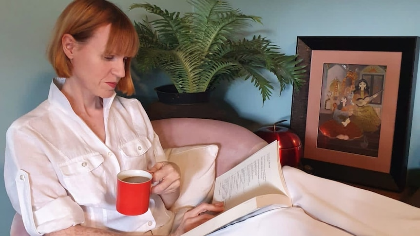 A woman sits on a chair with her feet up, a cup of tea and a book for a story on being the carer of a child with special needs