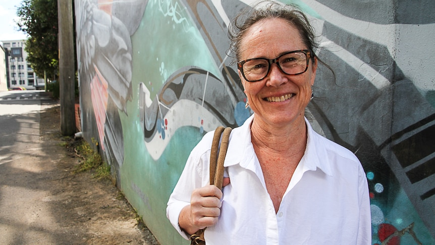 A middle-aged woman in a white shirt and glasses smiles in front of wall with graffiti.