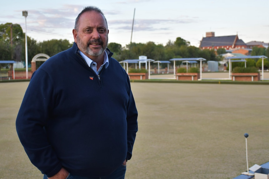 An Aboriginal man stands next to a bowling green in a small regional town.