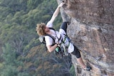A young man in a climbing harness hanging from a vertical rock face