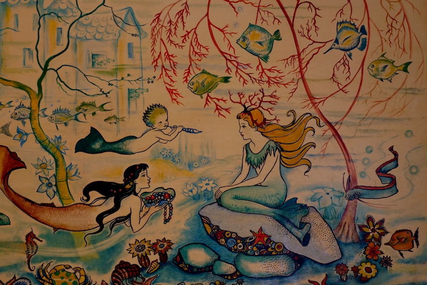 A colourful painting, depicting an undersea scene, including mermaids, fish and corals.