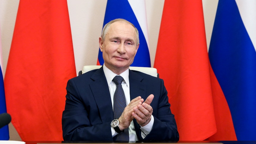 Vladimir Putin, sitting at a desk in front of Chinese and Russian flags, claps and smiles.