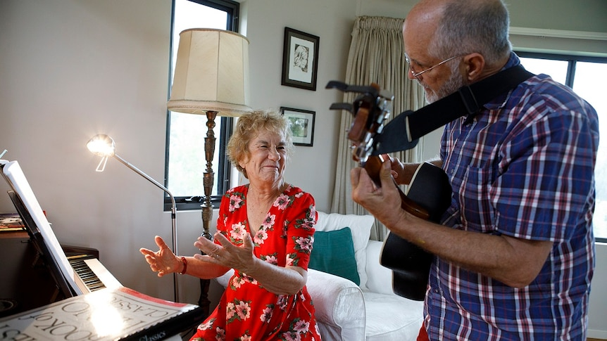 A woman sits at a piano and a man plays guitar for story on share housing when retired.