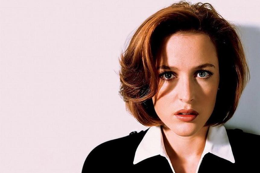 Gillian Anderson as Dana Scully stares into the camera
