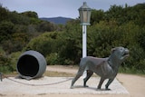 Picture of a statue of a vicious dog, with a lamp pose and barrel.