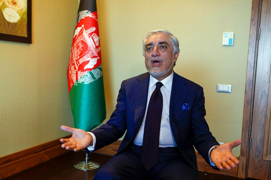 Abdullah Abdullah holds both hands out in a gesture while sitting in front of an Afghan flag.