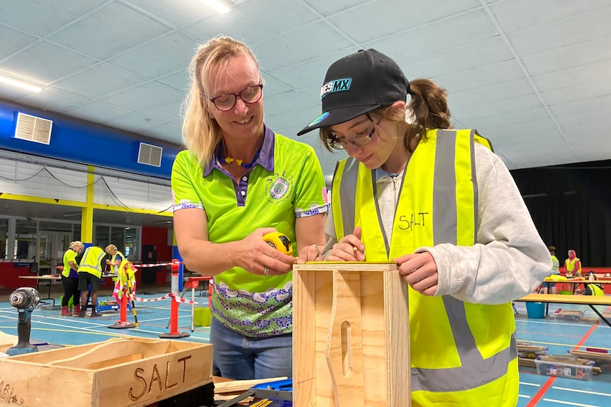 Two women with tools look over their woodwork