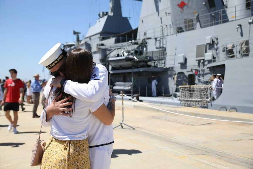 Two people embrace in front of a huge navy ship