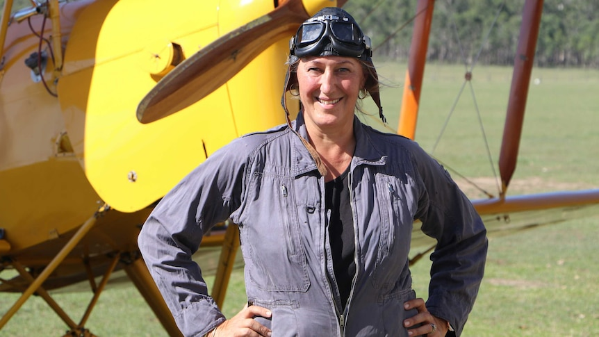 woman in pilot clothes standing in front of vintage plane