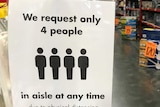 A sign in a Bunnings aisle during coronavirus restrictions reads 'We request only 4 people in aisle at any time'.