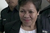 Maria Exposto seen with security staff at a Malaysian court.
