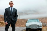 Daniel Craig, as James Bond, stands next to his Aston Martin in a scene from Skyfall.
