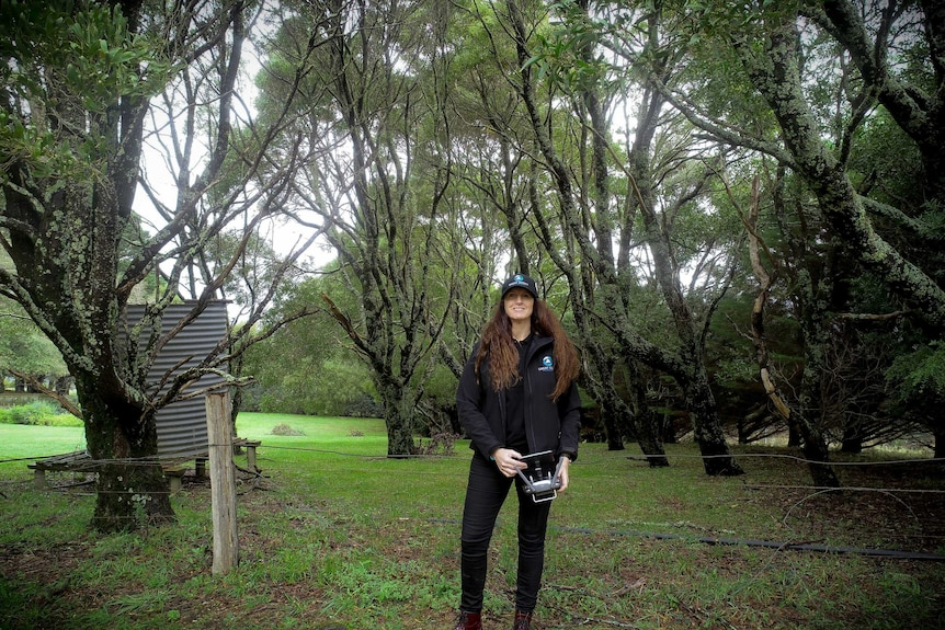 A woman standing surrounded by greenery with a camera.